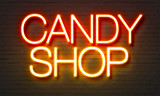 Candy shop neon sign on brick wall background.