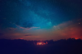 Fototapety Camping fire under the amazing blue starry sky with a lot of shining stars and clouds. Travel recreational outdoor activity concept.