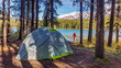 man camping lakeside in the rocky mountains