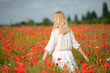 woman wearing white dress at summer blooming field. Back view