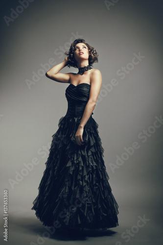 Jeune femme en robe de soirée regarde vers le haut, la main derrière la tête Poster
