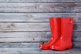 Red rubber boots on a grey wooden table - 137654531