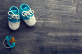 Toned photo of blue crocheted child bootees with little nipple on wooden background.