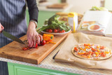 Close-up view of young woman s hands cutting vegetables on board for pizza according to recipe book