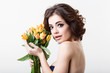 Portrait of beautiful dark-haired woman with flowers tulips.