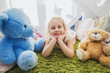 Little blonde child girl playing at home in her room with teddy bears