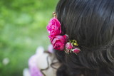 Beautiful peony flowers in hair of a happy bride on sunny summer wedding day. Long black curly hair, wedding hairstyle, close up. Copy space, blurred background