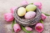 Fototapety Easter eggs in the nest. Spring flowers tulips.