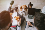 Young hipster couple home eating pizza with laptop and dog