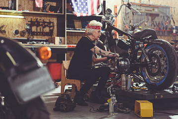 Serene grandmother repairing bike in mechanic shop