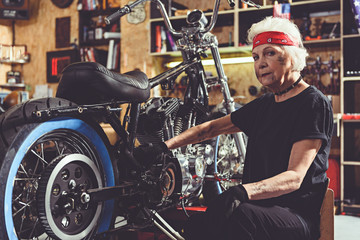 Serious retiree repairing bike in mechanic shop