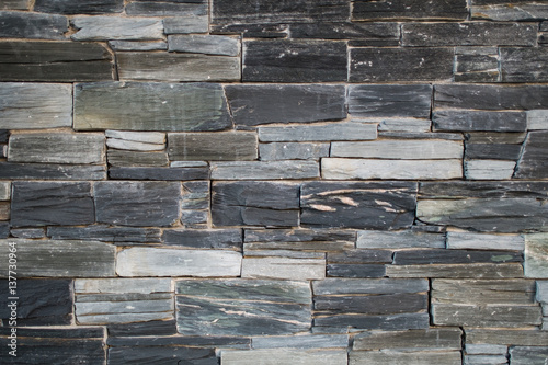 Poster Stenen Stone wall texture with black gray blue and white bricks