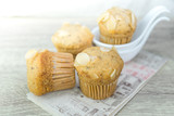 Homemade banana cup cake with sliced almond on wood background