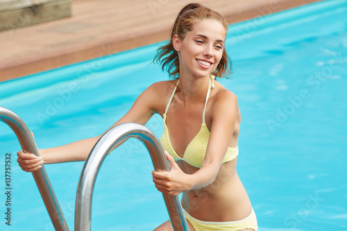 attractive young woman in pool, hot summer day, shot from above