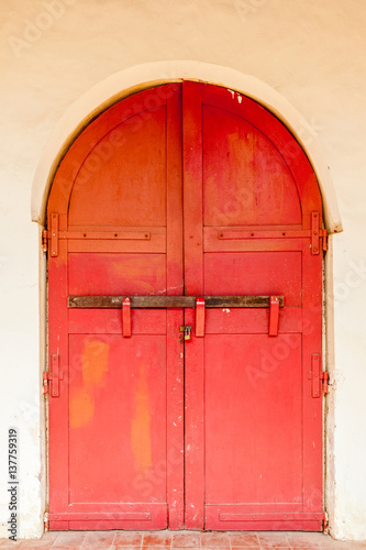 Traditional antique red wooden door double lock by padlock and wooden log. © mrcmos