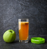 fitness bracelet glass with natural juice and apples on a stone against a dark background