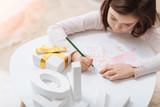 Cute creative girl focusing on drawing