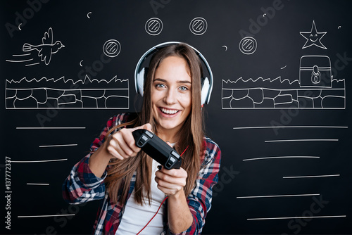 Poster Cheerful delighted young woman playing video games