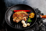 steak with mushrooms, red pepper, garlic in a skillet on coal with smoke