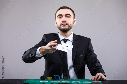 Poster Poker player in suit throwing two ace cards.