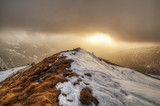 mountain landscape covered by snow with sun and low clouds at sunset