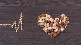 The cardiogram and heart made of nuts. The beating of the heart and the construction schedule cardiogram. Stop motion