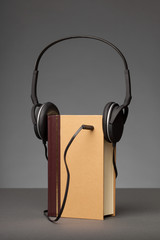 Vintage books on grey background with a Headphone, concept for Audio Books