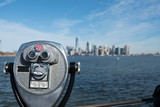 Tower viewer binoculars that look like a face on Liberty Island with New York Harbor and the Manhattan skyline in the distance.  Blue skies, bright beautiful day for New York sightseeing. - 137823948