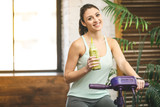 Young beautiful woman drinking vegetable smoothie after fitness at home. Fitness and healthy lifestyle concept with detox