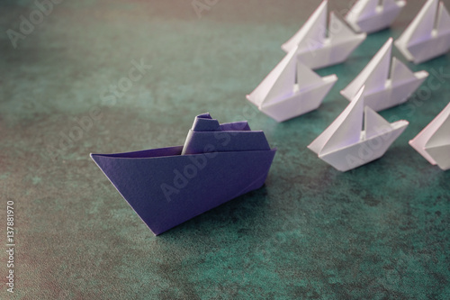 Poster Origami paper ship with small sailboats, leadership concept, toning