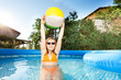 Girl playing with beach ball in the swimming pool