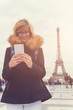 Cute girl using cellphone with Eiffel tower in the background, Paris - France.