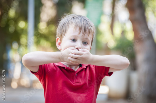 Serious little Caucasian boy closing his mouth with hands Poster