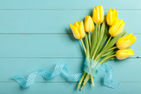 Yellow tulips on blue wooden background