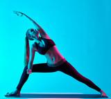 one caucasian woman exercising Utthita Parsvakonasana yoga exercices in silhouette studio isolated on blue background