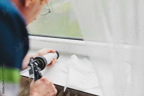 Backview of old man using a silicone tube for repairing the window