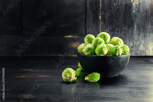 Fotobehang Brussel Ingredients Brussels Sprout on black wooden table. Selective focus