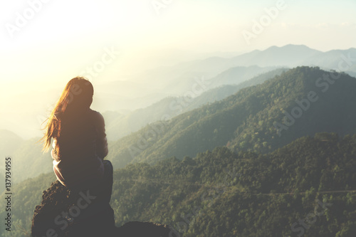 silhouette woman sitting on mountain in morning and vintage filter Poster