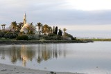 Architecture of Hala Sultan Tekken with water reflections and cloudy sky