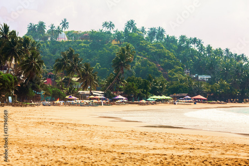 Beach with palms, beach loungers and sun-umbrellas in hot season