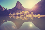 Beautiful mountain lake at sunrise with lens flare effect, color toned picture, Colorado, USA.