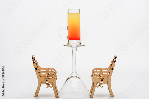 alcohol cocktail sex on the beach on wineglass with chairs Poster