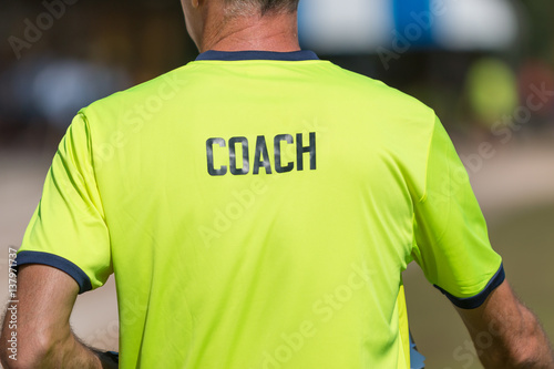 back of a coach's bright green color shirt with the word Coach written on Poster