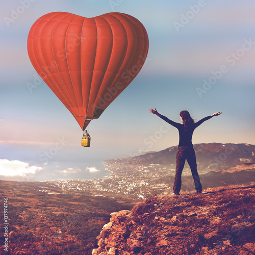 Poster Girl with hands up stand on top of mountain looking at big red air balloon heart shape flying in blue sky