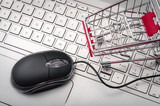 Online shopping and ecommerce concept with a optical mouse with cord and a shopping cart on a grey computer keyboard