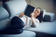 Ragazza legge libro sul divano a casa