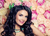 Happy Woman with Wavy Hair and Makeup on Flowers Background
