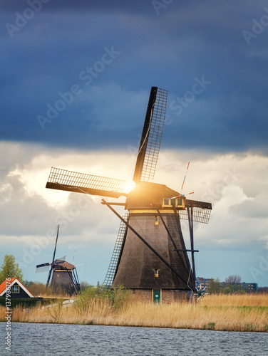Windmills against cloudy sky at sunset in famous Kinderdijk, Netherlands Poster