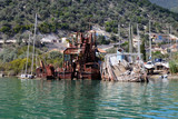 Seen from the sea sunken by the coast of Lefkada Island, Greece old ruined boats and a rusty dredge