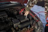 Mechanik podłącza kable rozruchowe do rozładowanego akumulatora. Odpalanie samochodu zimą przez kable rozruchowe. - 138004762